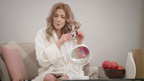 Portrait of cheerful Caucasian girl curling hair and looking in mirror Live Action