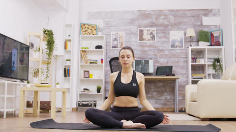 Young adult female doing yoga meditation in living room Live Action