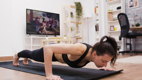 Young woman focused on her breathing while doing push-ups Live Action