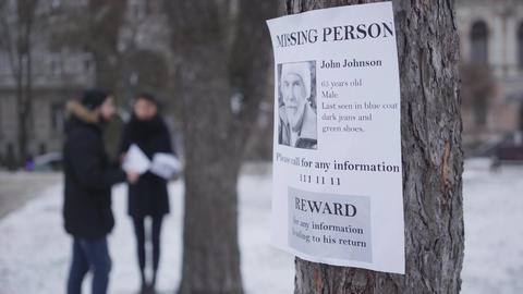 Close-up of missing person ad with information about lost senior Caucasian man Live Action