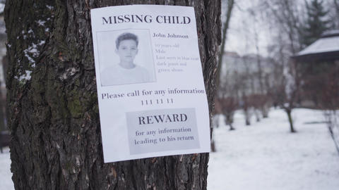 Missing Caucasian boy ad hanging on the tree in winter. Information about reward Live Action