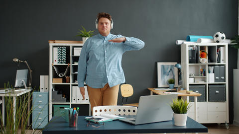 Portrait of handsome funny guy dancing in office room alone looking at camera Live Action