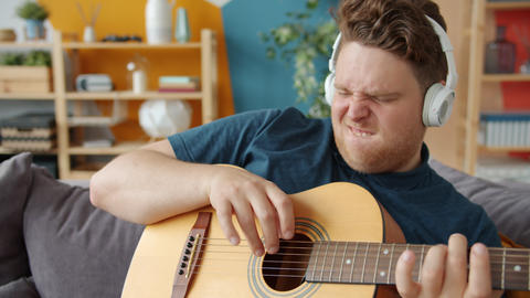 Playful guy playing the guitar at home having fun wearing wireless headphones Live Action