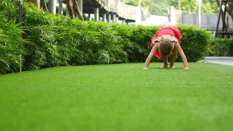Girl child tumbles sometime on green grass. Child make somersault Live Action