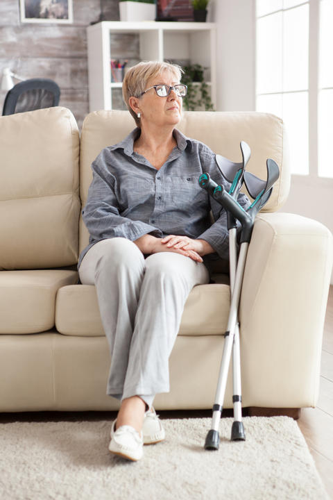 Retired lonely old woman sitting on a couch Photo