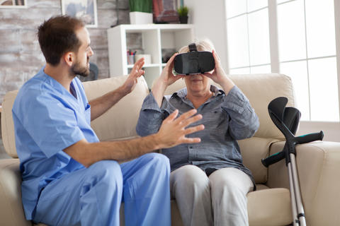 Older patient using virtual reality glasses in nursing home Photo