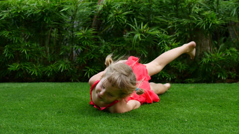 Girl child rides on the green grass. Walk in the fresh air, a girl rolls along Live Action