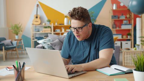 Slow motion of joyful businessman celebrating success at work using laptop at Live Action