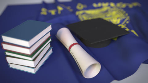 Graduation cap, books and diploma on the flag of Oregon. Higher education in the Live Action