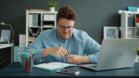 Portrait of playful young businessman having fun looking at camera in office Live Action
