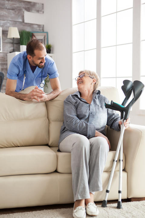 Old woman sitting on couch holding her crutches Photo