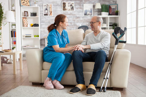Female doctor and senior man smiling to each other Photo