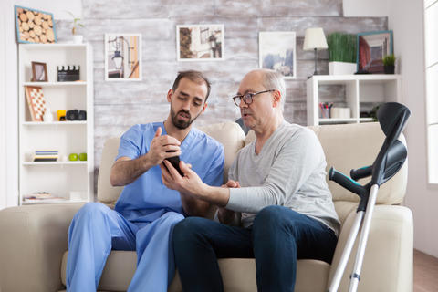 Young male nurse in nursing home holding phone Photo