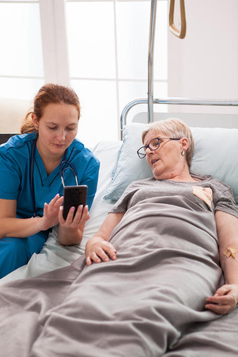 Female doctor helping old woman sitting on bed Photo
