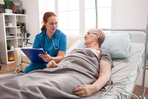 Old woman sitting in bed in nursing home Photo