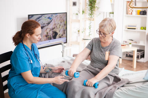 Health visitor helping old woman in nursing home Photo
