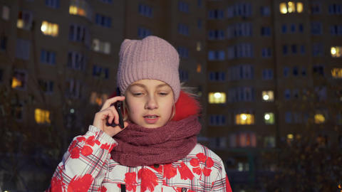 Teenager girl calling mobile phone at evening walk in winter street. Girl Live Action