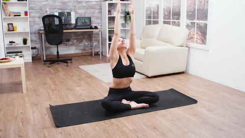 Young woman stretching her back sitting on lotus pose GIF