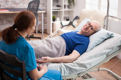 Male pensioner in nursing home talking with female doctor Photo