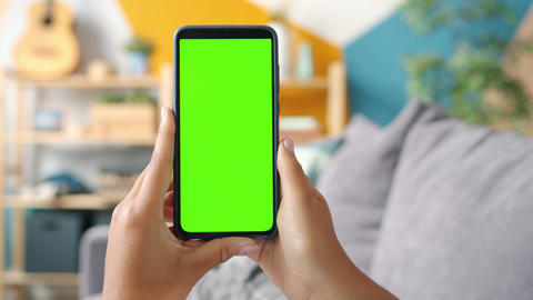 Close-up shot of green screen template smartphone in female hands at home Live Action