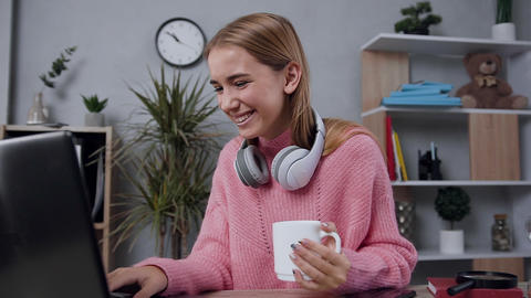 Pretty cheerful modern young woman in stylish sweater sitting at the computer 실사 촬영