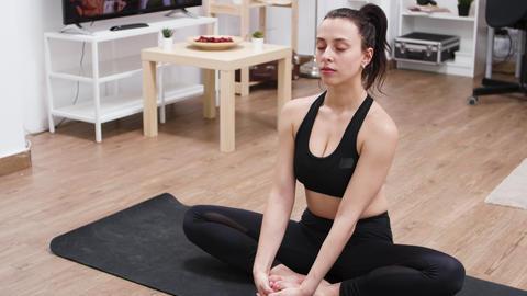 Pretty white woman doing lotus yoga pose on mat GIF