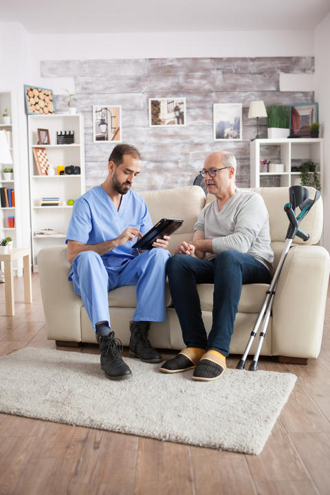 Young male doctor in nursing home taking notes on tablet pc Photo