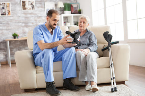 Young doctor sitting on couch in nursing home Photo