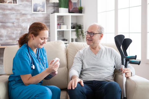 Female doctor in nursing home sitting on couch holding pills Photo