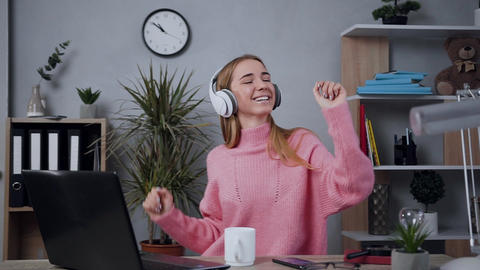 Smiling good-looking young woman in earphones dressed in pink knitted sweater Live Action