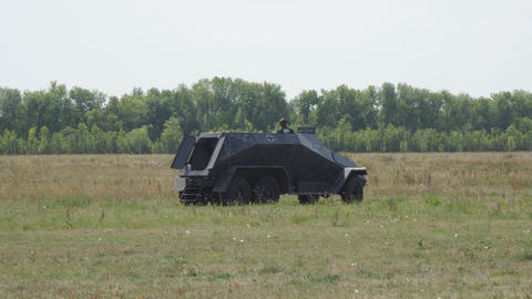 An old armored car from the second world war stands in a clearing Live Action