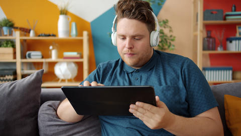 Serious guy wearing headphones using tablet touching gadget screen at home Live Action