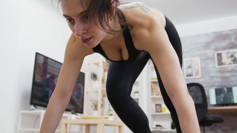 Young woman at home doing mountain climbers workout Live Action