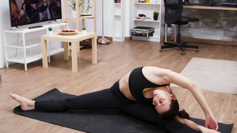Female yoga practitioner doing a split on the mat Live Action