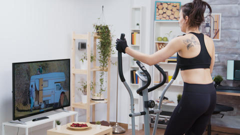 Young woman watching tv and doing a workout GIF