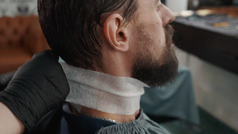Barber putting on mantle before haircut to bearded man in male salon Live Action