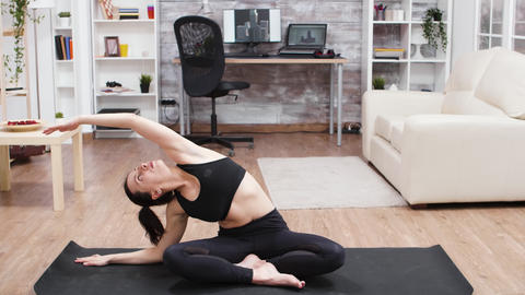 Young woman relaxing her back doing yoga pose GIF