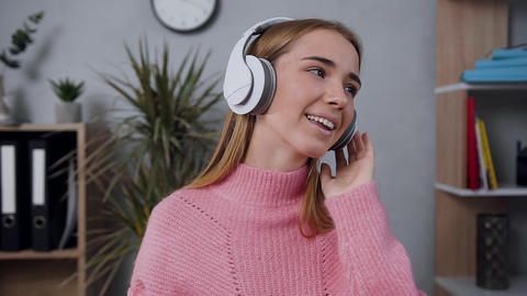 Pleasant good-looking young lady in stylish sweater wearing headphones listening Live Action