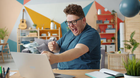 Playful guy receiving good news online using laptop celebrating success at home Live Action