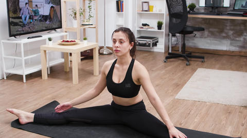 Young woman reaching out for the toe doing yoga practice GIF