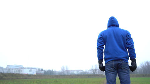 loneliness concept, man alone standing outdoors in park, rear view, wearing Live Action