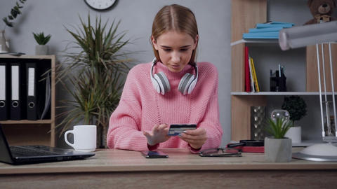 Appealing smiling blond girl in trendy sweater making online shopping using her Live Action