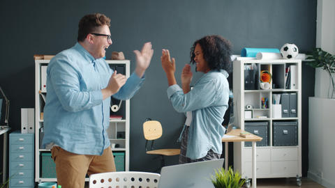 Afro-American lady and Caucasian man dancing clapping hands having fun in office Live Action