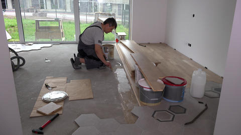 Skilled worker apply glue with trowel on floor for floorboard laying Live Action
