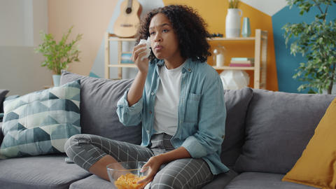 Emotional mixed race lady crying watching TV at home on couch holding snacks Live Action