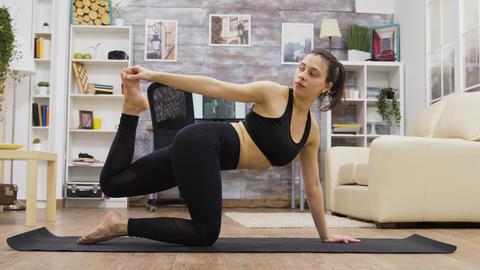 Pretty young woman doing balance yoga exercises GIF
