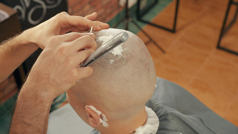 Cropped shot of barber shaving head of client with straight razor Live Action