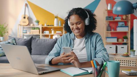 Joyful Afro-American lady touching smartphone screen listening to music in 실사 촬영