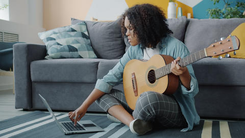 Joyful Afro-American lady playing the guitar in house on floor and using laptop Live Action