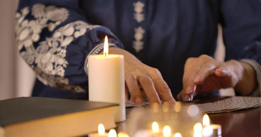 Close-up of lighting candle standing on the table as blurred female Caucasian Live Action